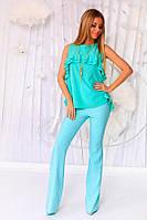 Шикарный брючный костюм состоит из легкой блузы с воланами и брюк. В комплекте декоративный кулон.