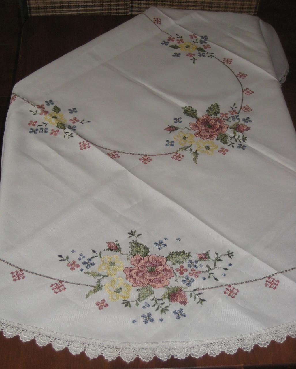 Біла скатертина оздоблена яскравою вишивкою хрестиком