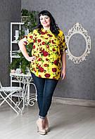 Желтая женская блуза с ярким цветочным принтом.