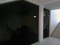 Стеклянная перегородка смаятниковой дверью и фрамугой из серого закаленного стекла