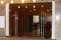 Стеклянная перегородка сдвумя маятниковыми дверьми и фрамугой из бронзового закаленного стекла