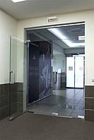 Стеклянная перегородка сдвумя маятниковыми дверьми и фрамугой из серого закаленного стекла