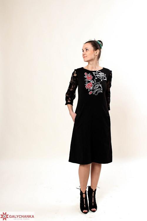 Элегантное платье черного цвета с гипюровым рукавом украшено вышивкой