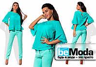 Эффектный женский костюм из легкой блузы с воланами и облегающих брюк голубой