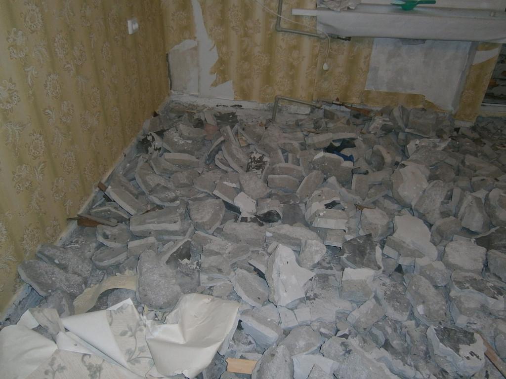 Фрагмент процесса демонтажа старой цементно-песчаной стяжки в квартире .