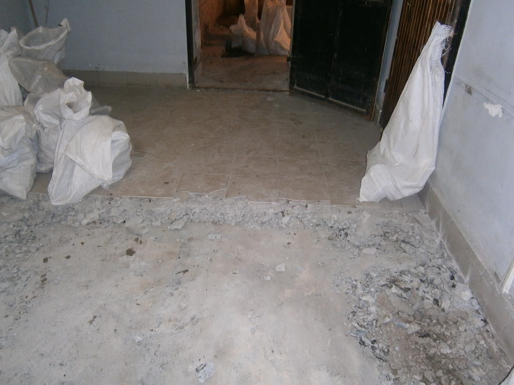 Демонтаж старого бетонного пола (покрытого местами кафельной плиткой) в подвальном помещении (три фотографии).