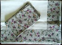 Льняная скатерть с салфеткой-подложкой украшена розовыми цветами.