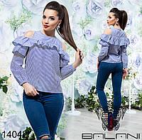 Блуза с открытыми плечами декорирована оборками.