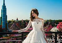 Сказочное свадебное платье А-силуэта с открытыми плечами и длинными рукавами и пышной юбкой со шлейфом