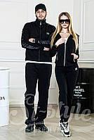 Спортивные черные костюмы для него и для нее. Костюм состоит из прямых брюк и олимпийки на молнии.