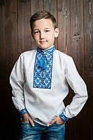 Красивая детская вышитая рубашка белого цвета с голубым орнаментом и бомбонами