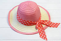 Плетенная шляпка украшена роскошным бантом с лентой в горошек
