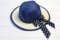 Женская шляпка украшена роскошным бантом с лентой в горошек
