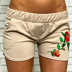 Коротенькие шорты в бежевом цвете декорированы аппликацией в виде цветка.
