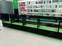 Витрины стеклянные с применением алюминиевого профиля, черного и зеленого дсп. Фасадная часть витрины распашные двери стекло, боковые части стекло, задняя стенка ДСП Зеленое, тумба с дверками Черное дсп с зеленной кромкой.