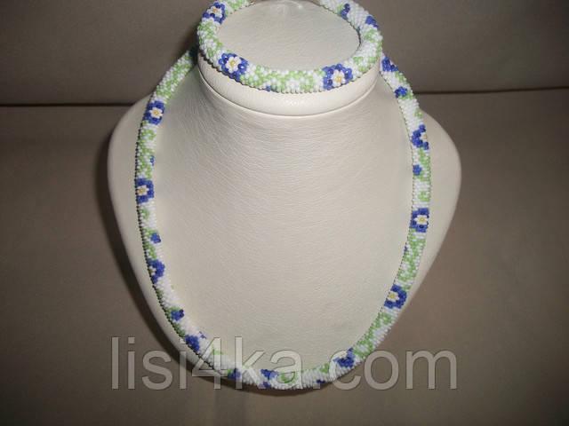 Узорный вязаный комплект жгутов из бисера с синими цветами на белом фоне