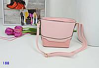 Женская светло-розовая сумочка на длинном плечевом ремне.