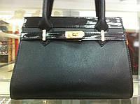 Хорошенькая маленькая женская сумочка черного цвета на коротких ручках с лаковой вставкой
