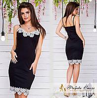 Облегающее черное платье декорировано белым кружевом