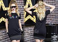 Платье полуприталенного силуэта в черном цвете. Украшением служит цветная вышивка из букв и цветов.