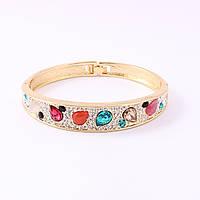 Браслет женский жесткий золотистого цвета декорирован разноцветными камнями