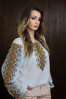 Нарядная вышитая блуза белого цвета с красивым узором на рукавах