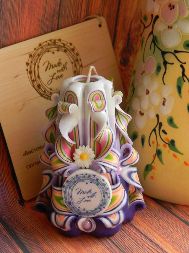 Резная свеча с логотипом и украшениями из ромашек.