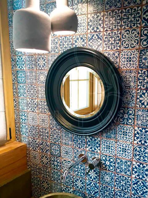 Круглое настенное зеркало в раме черного цвета.
