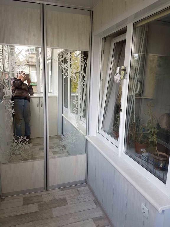 Остекление балкона с глухой стенкой, зеркальный шкафом-купе во внутренней отделке.