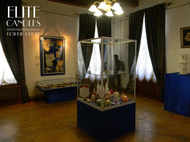 Выставочная зала с резными свечами и подсвечником.