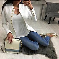 Женский пиджак на пуговицах и декорирован по бокам карманами черный и белый