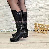 Кожаные женские зимние сапоги на невысоком каблуке, декорированы ремешком.