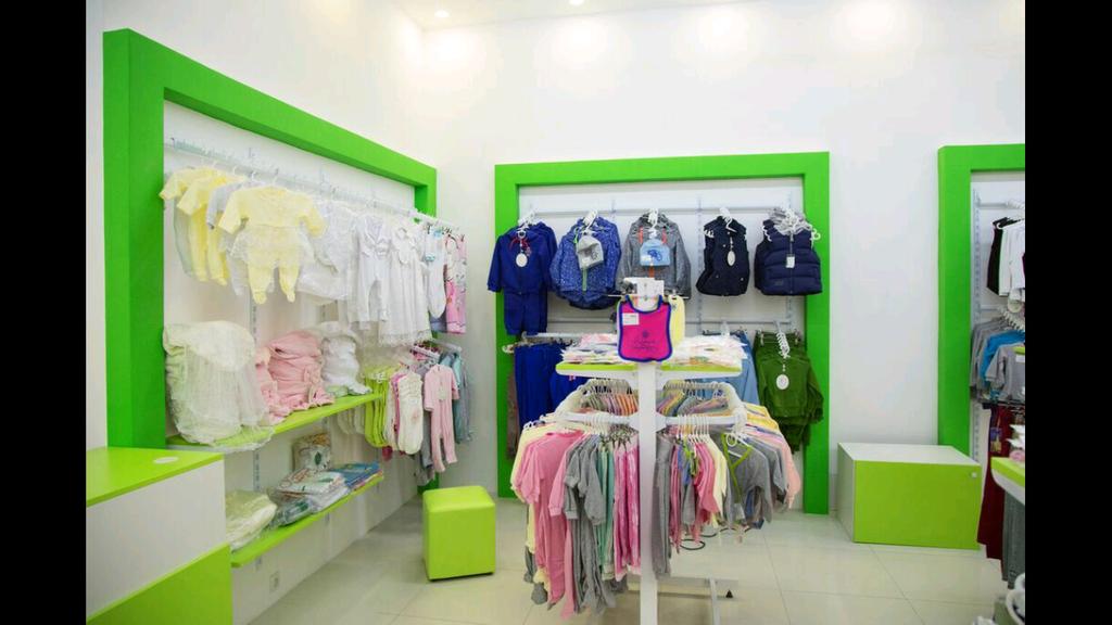 """Тут в центре островная стойка для одежды и стойки системы """"Вариант"""" с товаром."""