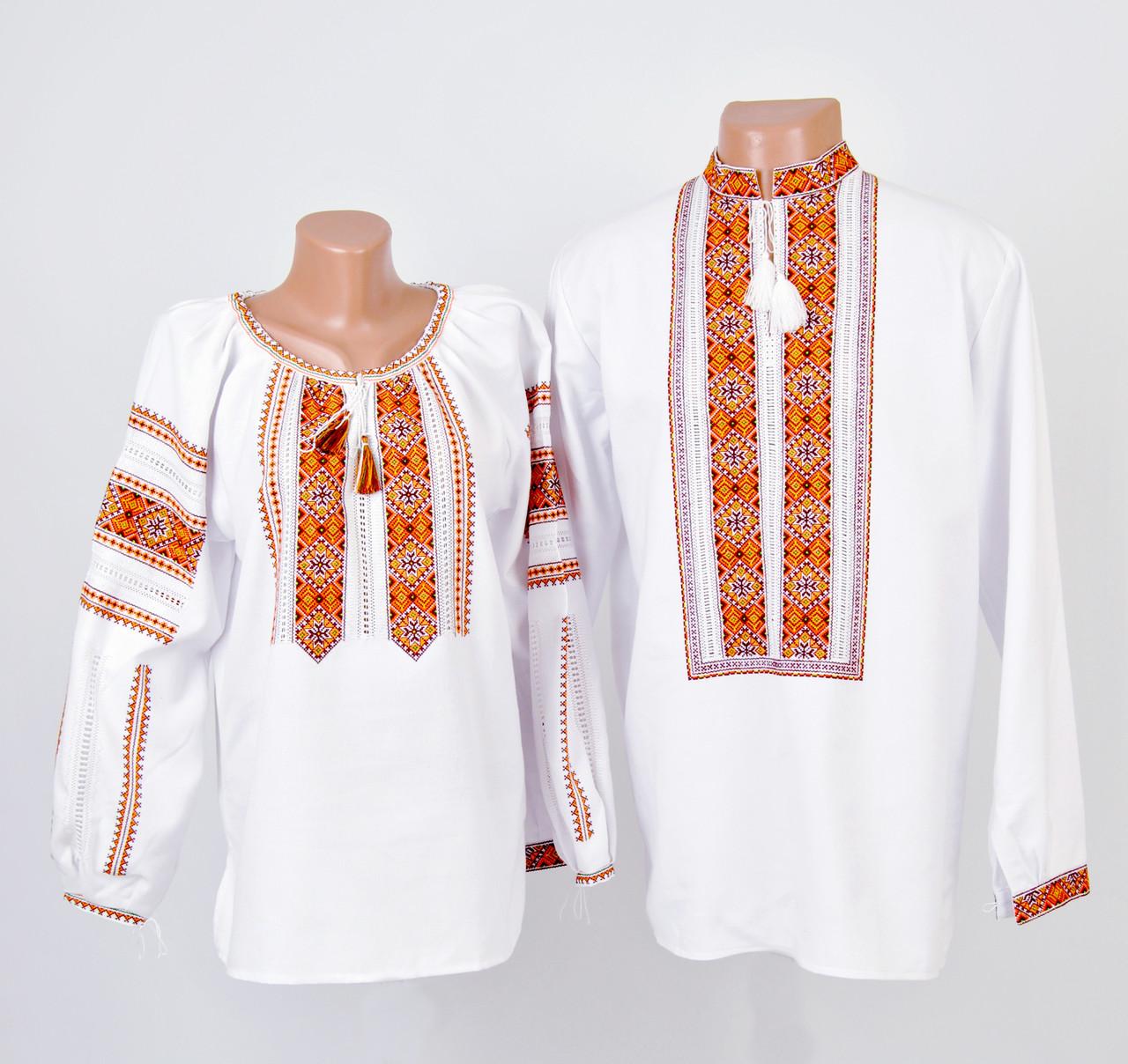 Пара вишиванок білого кольору з оранжевим орнаментом ручної роботи