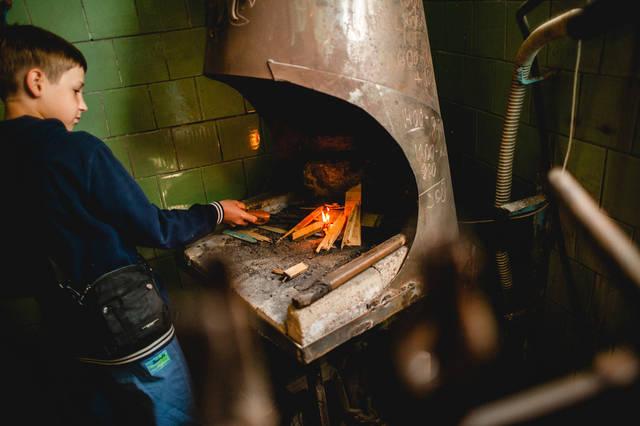 Дети учатся разводить огонь в кузнечном горне