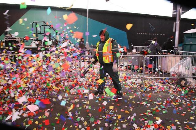 Рабочий коммунальной службы очищает площадь от конфетти после городской ярмарки