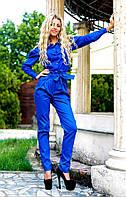 Модный костюм-двойка, блуза на пуговицах и брюки с карманами по бокам.