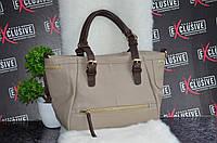 Женская сумка с коричневыми ручками.