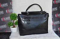 Черная кожаная сумка в деловом стиле.