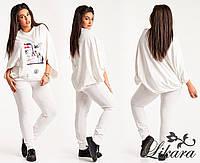 Спортивный костюм молочного цвета: штаны и кофта свободного кроя.