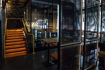 Вид на холодную комнату. Через стекло видны пивные кеги и гидравлическое оборудование.