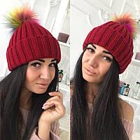 Стильная тёплая женская вязаная шапка с цветным бумбоном бордовая
