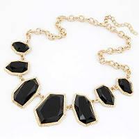 Колье на золотой цепочке с крупными черными камнями необычной формы в золотой оправе