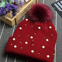 Стильная вязаная женская шапка с бубоном декорирована жемчугом и бусинами