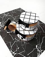 Круглый набор интерьерных коробок ручной работы белого цвета в чёрную клетку