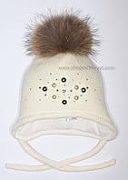 Молочная шапочка Марта с помпоном из меха енота