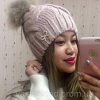 Женская вязанная шапочка с бубоном из меха енота