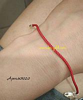 Красная нить на руку с серебряной застежкой.